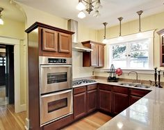 small but sharp u shape. window trim. double ovens...need to bring the cabinets all the way up to ceiling