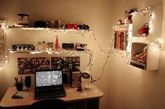 I love all the shelves and the tiny Christmas lights strewn around. The desk is small but neat. The two photo collages (one in color and one in black white) are a very good idea too.