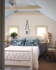 This bedroom illustrates how blue can be used in a fresh, clean, American way, mixed with white linens and light woods to evoke breeze-blown New England seaside cottages. An antique spool bed painted white and laid with a pure white spread has blue floral pillow shams. Behind the bed, a blue botanical cyanotype is framed in white, suspended on a medium blue ribbon. The ceiling is painted sky blue for a feeling of being up in the clouds.
