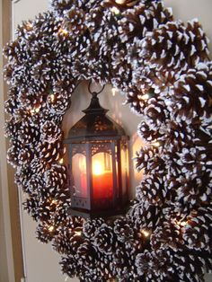 Pinecone wreath and lighted lantern create a festive holiday welcome.