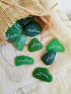 Featuring Hanwriting's dreamy calligraphy, these natural place cards are made from frosted sea glass in shades of green and teal.