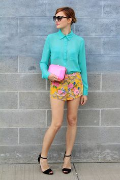 colour block blouse & floral shorts with a splash of pink clutch.