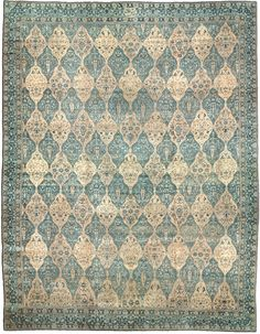 A North Indian carpet BB2023 - An early 20th century North Indian antique rug, the field with an overall beige and green diamond lozenge lattice ...