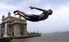 Un hombre salta en las aguas del Mar Arábigo, cerca de la Puerta de la India en Bombay
