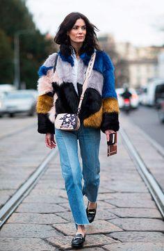 Mulher posa para foto de street style usando camisa branca, calça jeans reta azul, casaco faux fur colorido, mocassim clássico preto
