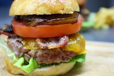 classic beef burger with cheddar, tomato, lettuce, bacon and caramelised onions on a home-made delicious bun.