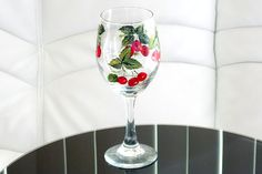 Bright and beautiful wine glass featuring red cherries with green leaves painted all around with acrylic paint. Makes a great gift - especially, if purchased in a pair. May also be used in decoration as an accent.    This wine glass is 8 inches (20.3 cm) tall, the stem is 3.5 inches (8.9 cm) long, the diameter of the bowl is about 3 inches (7.6 cm). It can hold 14 oz (414 ml).    CARE INSTRUCTIONS: We recommend hand washing without using harsh chemicals or abrasive materials or objects…