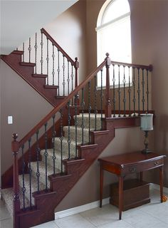 Staircase Remodel.  From all carpet and light oak to iron and dark stained wood with a carpet runner.