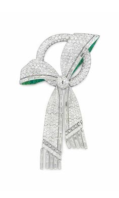 AN ART DECO DIAMOND AND EMERALD BOW BROOCH: Designed as a circular-cut diamond open circle, wrapped within a circular and baguette-cut diamond bow, trimmed with calibré-cut emeralds, suspending baguette-cut diamond tassels, circa 1930, 4 1/2 ins., with French assay marks for platinum and 18k gold. Via Christie's.