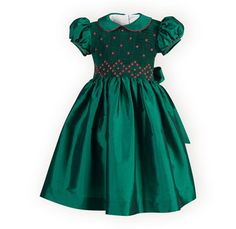 The perfect holiday dress in shimmering emerald poly taffeta. Waisted dress with delicate hand-smocked bodice has tiny red flowers creating a diamond