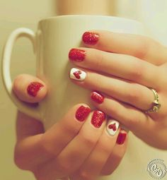Short red glitter nails with white accent nail plus red heart. Perfect for a simple Valentine's manicure
