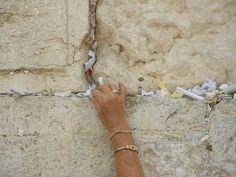 Leaving a written prayer in the Western Wall.  Jerusalem, Israel.