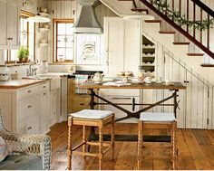 country style kitchen & salvaged cast iron table used as an island ~ I'm lovin this layout & mostly the stairs & storage!!
