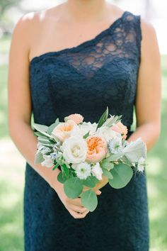 A beautiful white and peach bouquet pairs perfectly with a navy bridesmaid dress. | Aaron & Jillian Photography