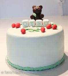 Green cake with strawberryes, flowers and brown teddybear