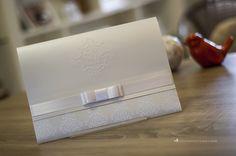 Convite de casamento clássico e elegante com padrão adamascado e brasão em relevo seco.