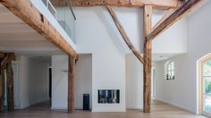 Herindeling van woonboerderij met behoud van originele houten spanten, open woonkamer tot kap met vide en slaapkamer met open badkamer met hoogteverschil.