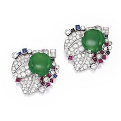 Pair of Platinum, Jade, Colored Stone and Diamond Clip-Brooches, Cartier, London Centering two button-shaped jade cabochons, within foliate surrounds set with baguette, old European and single-cut diamonds weighing 5.50 carats, further decorated with calibré-cut rubies and sapphires