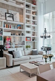 Love the tall bookshelves and hanging chandelier. High ceilings, floor-to-ceiling windows. Neutrals with color-pops in accessories.