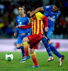 Lisandro Ezequiel Lopez (R) of Getafe CF holds the face of Lionel Messi (L) of FC Barcelona during the Copa del Rey Round of 8 second leg match between Getafe CF and FC Barcelona at Coliseum Alfonso Perez on January 16, 2014 in Getafe, Spain.
