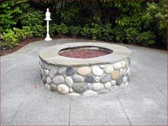 river rock fire pit with travertine around the top...would like a matching sitting wall to go around the corners of the patio...perfect coloring...