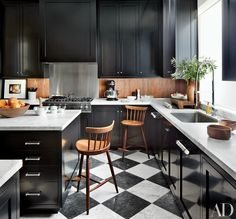 A walnut backsplash and vintage George Nakashima barstools add warmth to a kitchen designed by Dan Fink that features black cabinets and checkered floors.  RELATED: Get more kitchen renovations tips and ideas from AD.