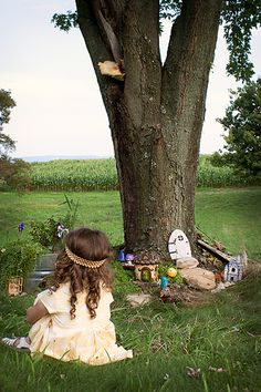 Delightful kid-made FAIRY GARDEN around a tree trunk from The Magic Onions Blog.