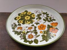 Vintage Mid Century tray Floral tray White green orange yellow floral tin tray 60s Mod tray This is a vintage tin tray with mod floral pattern.  Measurements: 30cm in diameter, approx 3cm deep Condition: This tray has been used a lot but still has a lot of life left. There are a lot of signs of wear--paint rubs and scratches The colors of the flowers are still very vibrant and clear.