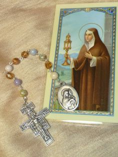 This Chaplet has been created with 7, 6mm Picasso beads, and 3 6mm fire polished faceted Czech crystal beads. It is approx. 8.25 inches long. It has a medal of Saint Claire on one end and a San Damiano Cross (The Crucifix of the Franciscans) on the other end. All medals are Italian made. It is very sturdy as I only work with heavy duty eye pins and rings. This chaplet comes with complete instructions on praying the rosary (this is a single decade Rosary Chaplet) and a St. Claire laminated…