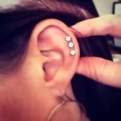 Triple helix piercing with studs. on The Fashion Time http://thefashiontime.com/5-cute-fun-ear-piercing-ideas/#sg10