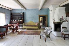 Tuvan kauniissa saviseinissä on alkuperäinen sininen väri. Puusohva on perintökalu, mutta lautashylly ja sivupöytä ovat Tapiolan hankkimat.