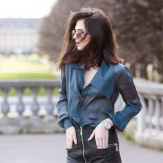 A sheer blouse is worn tucked into a zipper leather black skirt with aviators and a watch.