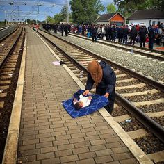 A Syrian refugee woman changes her daughter's diaper while she and other migrants stand behind the police waiting a train to board in Tovarnik, Croatia. #refugeecrisis #syrian #refugees #dailylife #europe