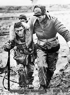 Canadian rifleman, Private Morris J Piche of the 2nd Battalion, Princess Patricia's Canadian Light Infantry, is helped to an aid station beh...