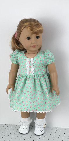 $16 A sweet spring dress for your doll. This dress is a cotton fabric with a mint green back round and a small pink flower print on it. The bodice is lined. The short sleeves have elastic at the bottom. White trim is sewn to the bodice front, by MySewYou