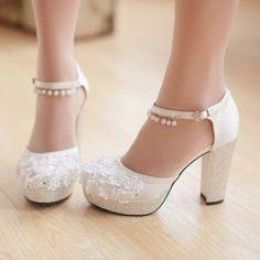 Estos tacones anchos no se clavarán cuando camines. Delicados zapatos de tela con detalles de flores en apliqué y tacones con plataformas cubiertos de strass. Un look inspirado en las guillerminas con una tira con perlas alrededor del tobillo.
