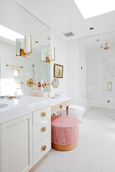 White contemporary bathroom fitted with gold accents displays a round pink stool at a wood makeup vanity.