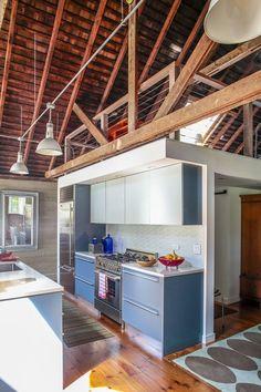 A cozinha da residência - que tem um projeto da década de 1970 e leva a assinatura do arquiteto Tod Williams - conta com muita luz natural, décor simples e detalhes de vigas aparentes.  Fotografia: Eric Striffler/ The New York Times.