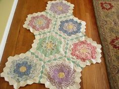 Grandmothers_flower_gard_quilt - This is the kind of quilt that my great-grandmother made as I was growing up in the 1960's. She cut out a piece of cereal box for each hexagon to hold it in place. Each piece had to be sewn by hands.