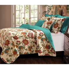 Flowered vines grace this updated tropical quilt in gold, olive green, red and turquoise on an antique white ground while the fabric bound edges and reverse have an all-over solid turquoise color. The quilt is oversized for deep mattress coverage.