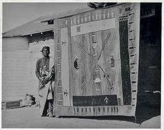 Hosteen Klah (aka Hastiin Klah) standing by a woven rug he made in a sandpainting design - Navajo - before 1937