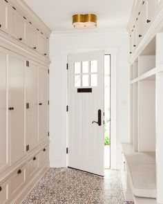 Fabulous long mudroom features a gold clover flush mount, Large Basil Flush Mount, illuminating a wall of floor to ceiling light taupe mudroom locker cabinets adorned with bronze hardware facing a open mudroom lockers and a built in bench with overhead cabinets across from a blue and gray mosaic tiled floor.