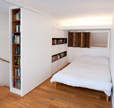 Instead of a space-displacing bedroom door, a pair of panels (sandwiching a bookshelf) slides over the opening to the room. In the process, this movement reveals clothing storage space while concealing a stack of books .