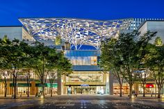The main entrance is flanked by two large volumes protruding horizontally from both sides, and is covered by a large steel canopy resembling the trees and ...