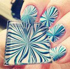 A radical and sassy water marble nail art design in white, blue and green blue polish patterned together to create intersecting lines.