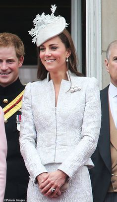 June 14, 2014: Trooping of The Colour Catherine Duchess of Cambridge wore an ice blue heavily textured with a pebble effect suit designed by Sarah Burton for Alexander McQueen. Catherine also wore a bespoke Jane Taylor hat and used her own McQueen clutch. Catherine also wore an new brooch consisting of two rows of oversized pearls. Catherine also wore Kiki McDonough hoops and Annoushka pearl drops.