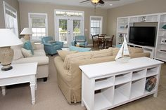 Tan, white, and sea blue beach house living room with nautical decor