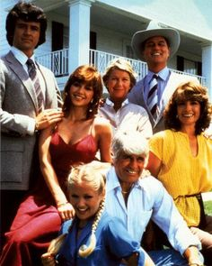 The original cast of Dallas in front of Southfork Ranch. Clockwise from top are: Larry Hagman (in cowboy hat), Linda Gray, Jim Davis, Charlene Tilton, Patrick Duffy, Victoria Principal, and Barbara Bel Geddes.