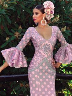 Elegante vestido de flamenca confeccionado en tejido de Strech, que combina lunares con brocados. Adornos de bolillo en color gris.
