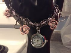 Silver bracelet with pink polymer flowers, charms and a working pendant timepiece. Great for all occasions, work or a wedding